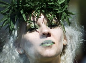 A women blows smoke after using a pipe as she takes part in the annual marijuana 420 smoke off at Dundas Square in Toronto on Friday, April 20, 2012. All around the world pro-marijuana supporters are gathering in support of cannabis. (AP Photo/The Canadian Press, Nathan Denette)