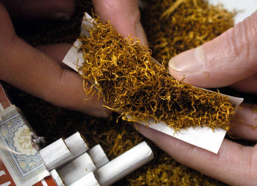 Two hands rolling a cigarette are seen next to a pack of ready-made cigarettes in Hamburg, Germany, 10 February 2004. Self-made cigarettes are still cheaper than buying packs of cigarettes.
